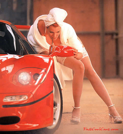 Pretty lady getting ready with side view mirror on sports car