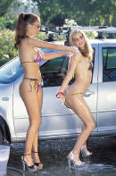 A couple young ladies washing their vehicle, and keeping it looking good.