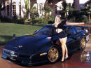 Black Corvette with very cool gold wheels and pretty lady