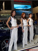 three models at what appears to be a car show in Japan.
