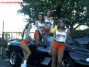 Hooters girls with a Ford Mustang convertible.
